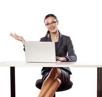 mulher de negócios sorridente, sentado à mesa com o laptop foto