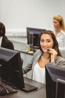 agente de call center sorridente, falando no fone de ouvido foto