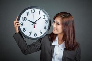 empresária asiática mostrar um relógio no ombro e sorriso