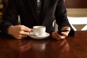 homem tomando café e usando um telefone celular. foto