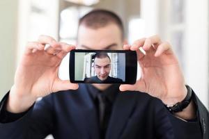 homem de negócios, tendo selfie