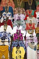 moda roupas bonitas penduradas no bazar do mercado de rua da Ásia foto