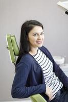 retrato de menina com sorriso saudável na cadeira odontológica foto
