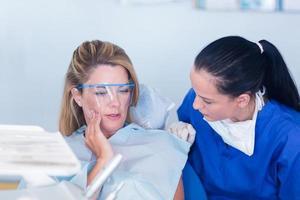 dentista falando com o paciente sobre dor de dente foto