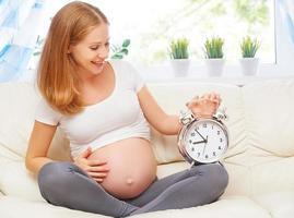 conceito de gravidez. mulher grávida feliz com um despertador foto