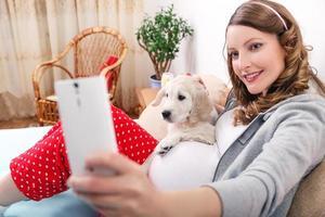 mulher grávida com seu cachorro em casa