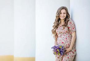 linda mulher grávida com um ramo de flores foto