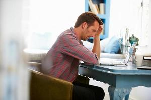 estressado homem na mesa no escritório em casa com laptop foto