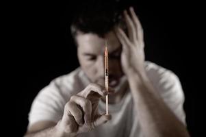 homem viciado em drogas com seringa de heroína ou cocaína deprimida foto