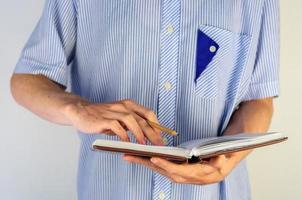 homem de camisa, escrevendo em seu caderno