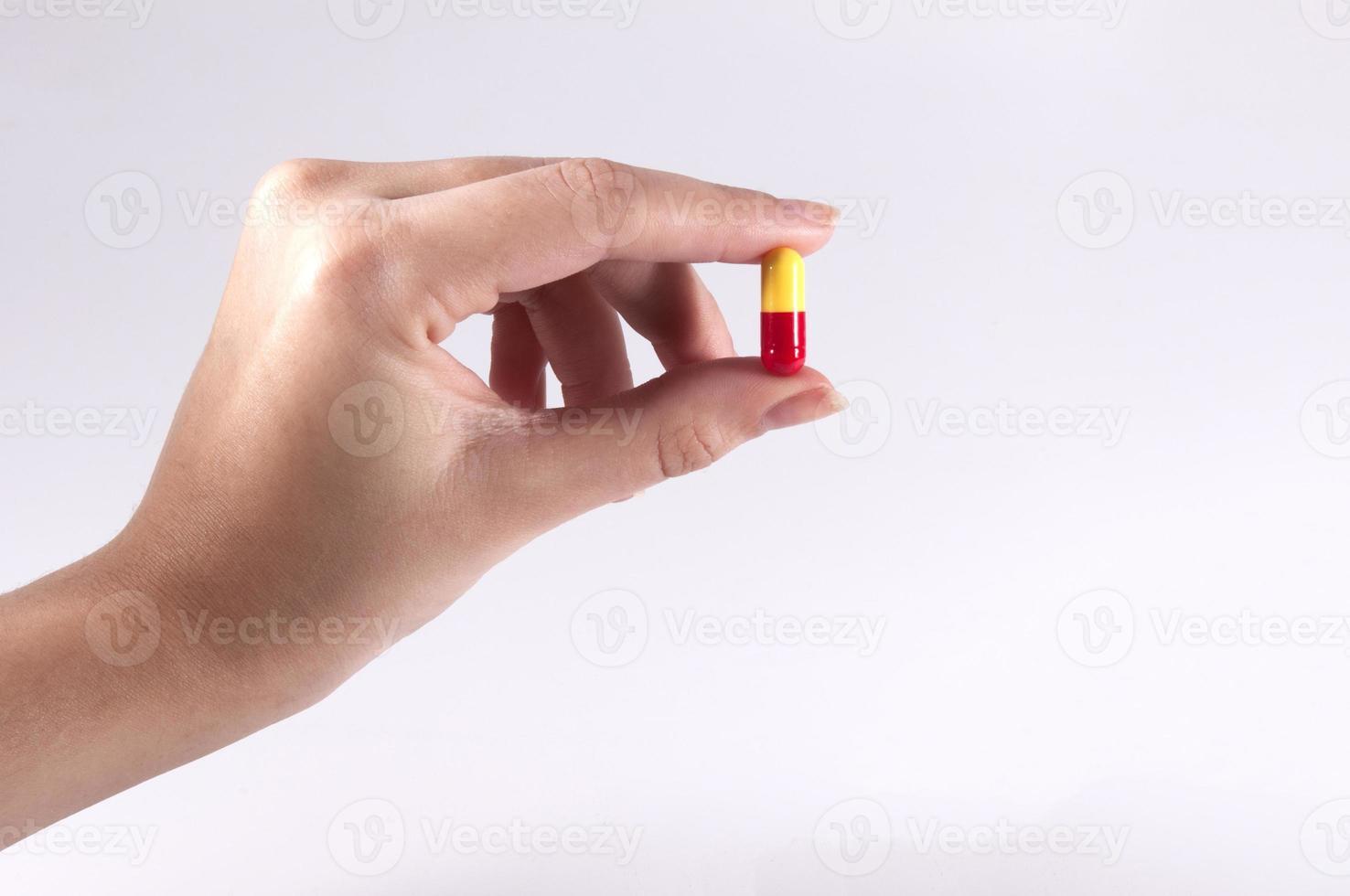 kaukasische Frau, die eine Pille auf weißem Hintergrund hält foto