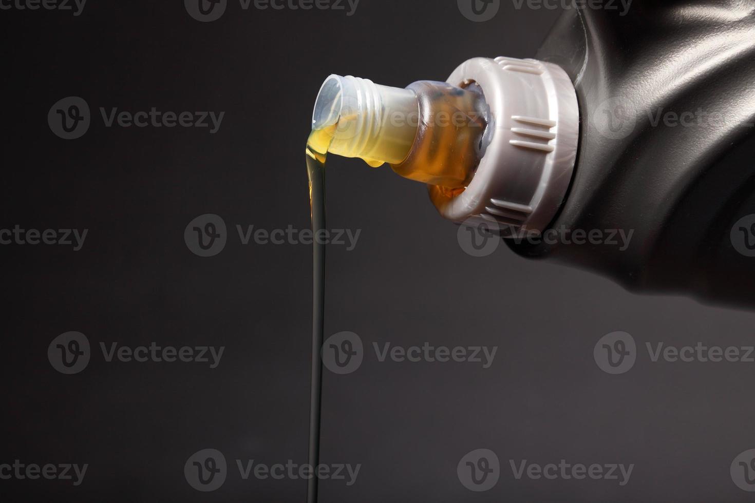 Dose mit Automotoröl, das schwarzen Hintergrund gießt foto