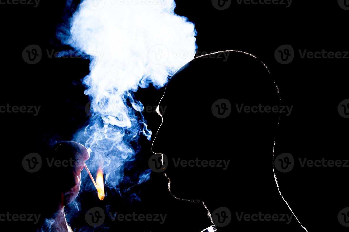 Silhouette eines Mannes, der die Zigarette im Dunkeln anzündet foto