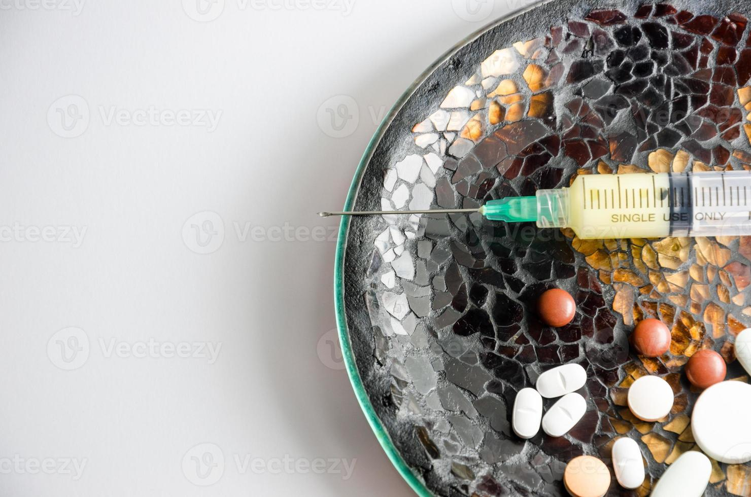 Spritze und Pillen auf einem Teller foto