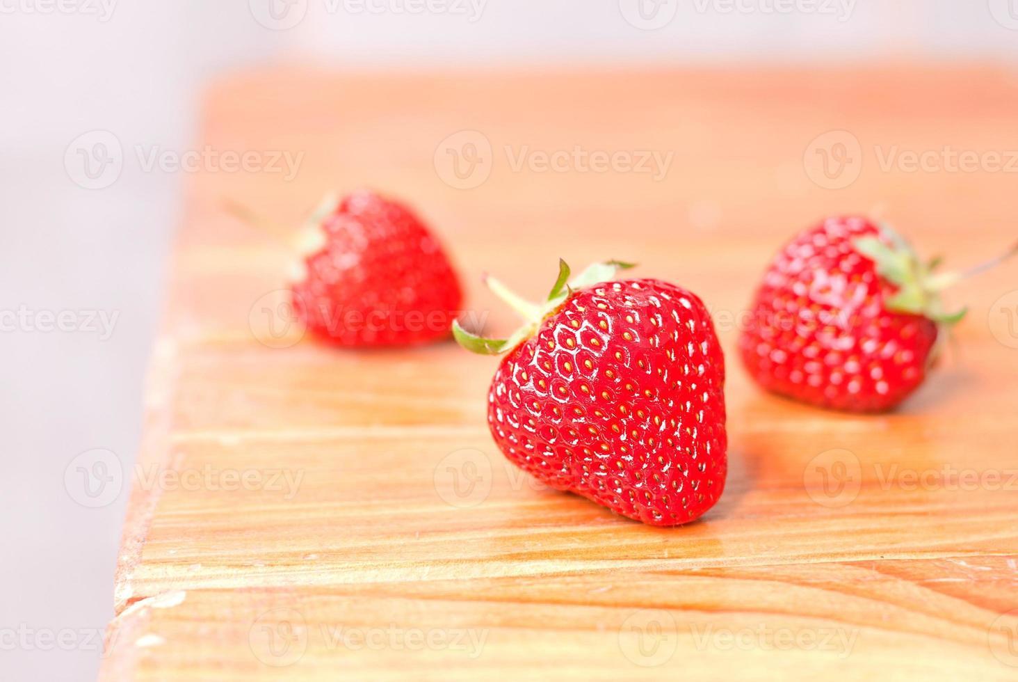 drei Erdbeeren auf dem Tisch, Seitenansicht foto