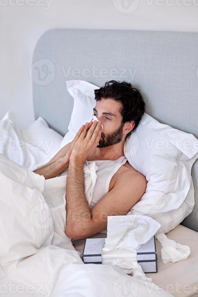 Ein kranker und depressiver Mann mit Papiertaschentüchern im Bett foto