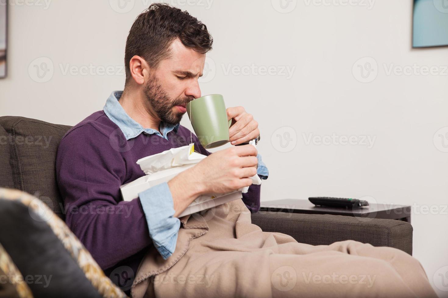 Mann mit einer Erkältung trinkt etwas Tee foto