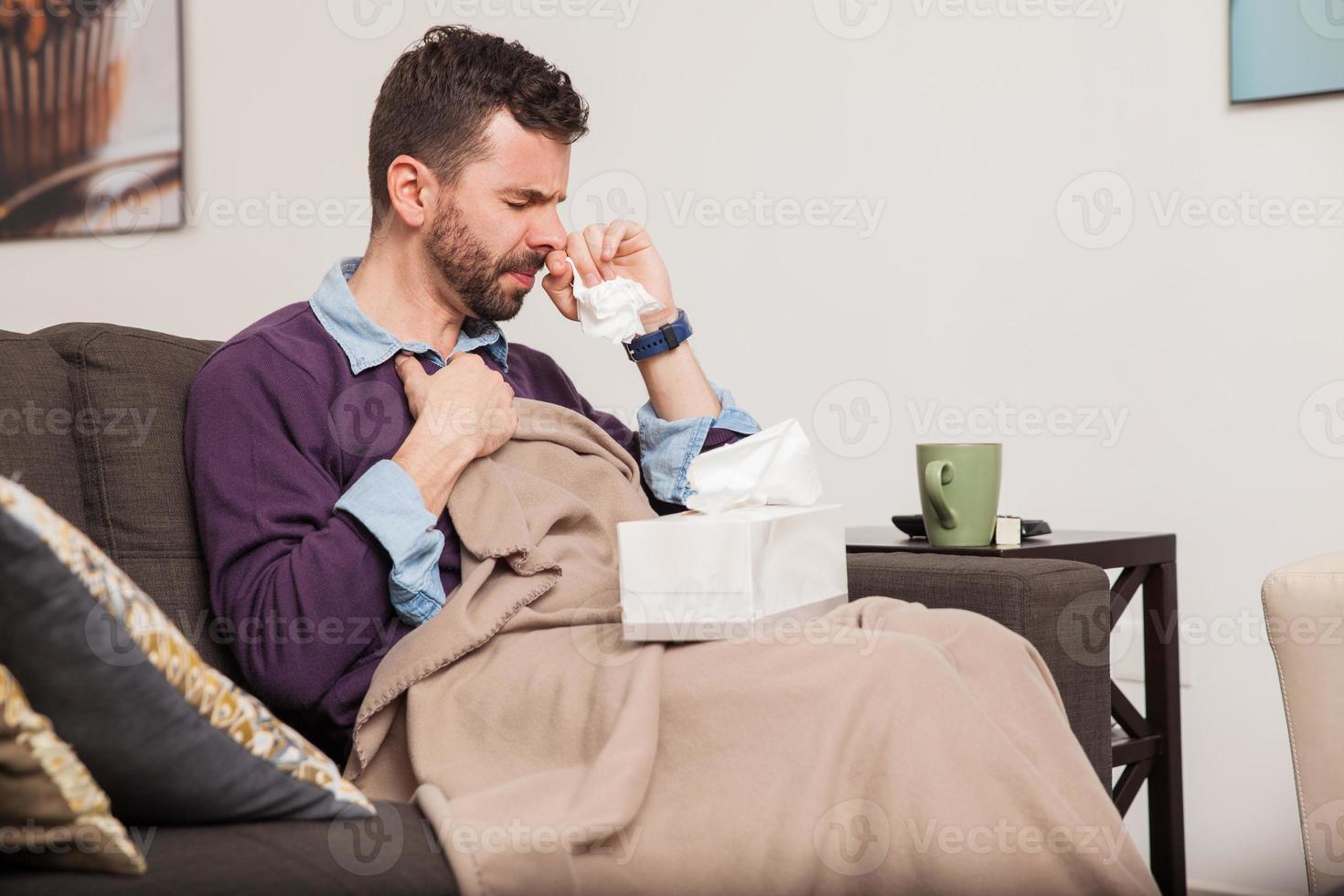 Mann kämpft zu Hause gegen eine Erkältung foto