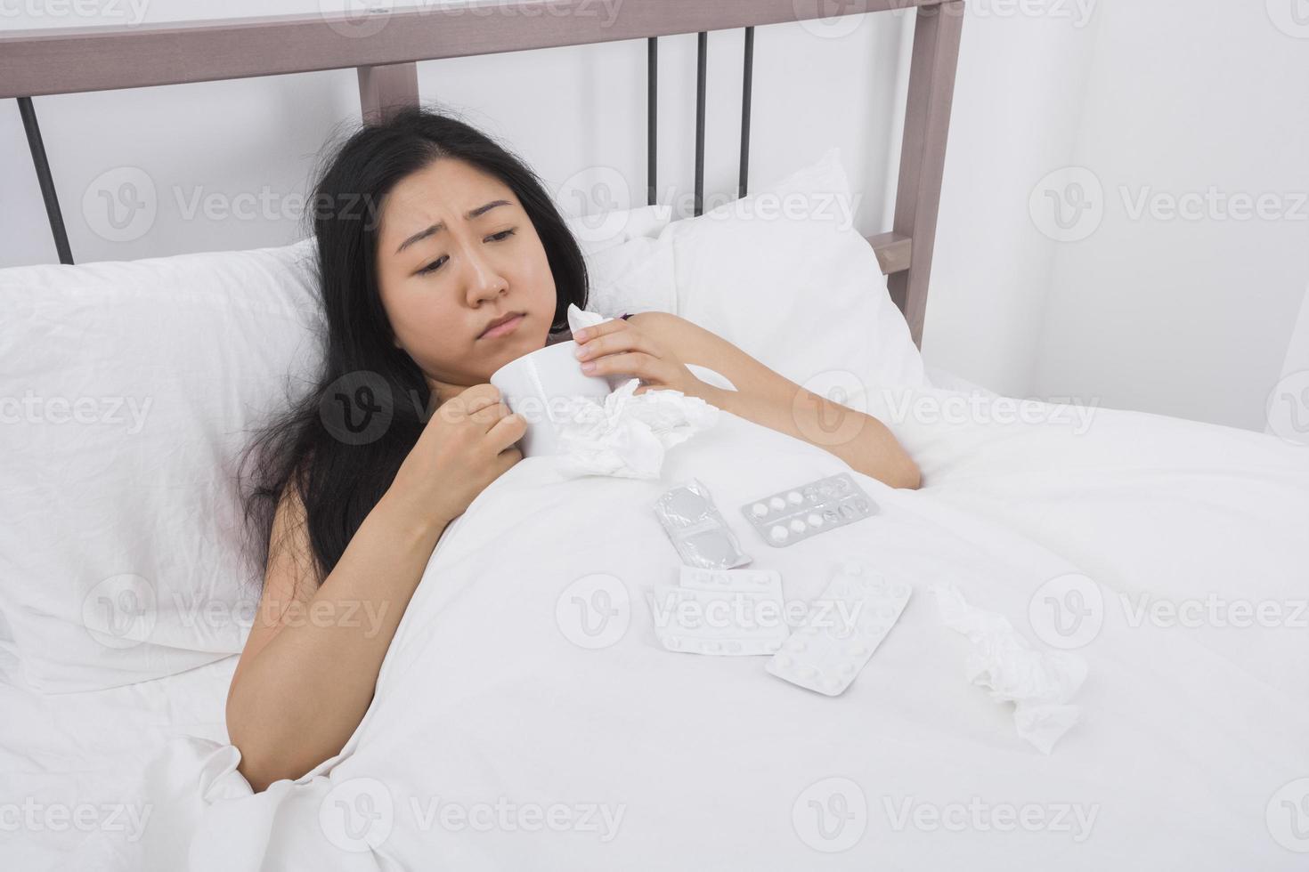 Frau, die an Kälte leidet, die Kaffee im Bett trinkt foto