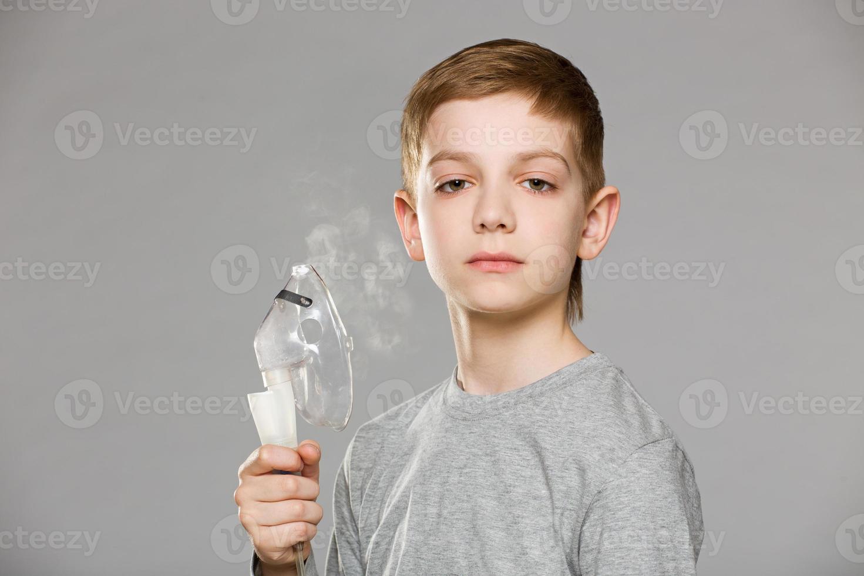 unglücklicher Junge, der Inhalatormaske hält, die Rauch auf grauem Hintergrund freigibt foto