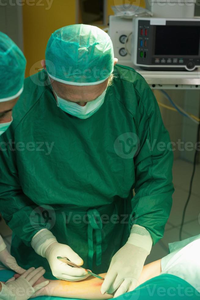Chirurg, der einen Patienten einschneidet foto