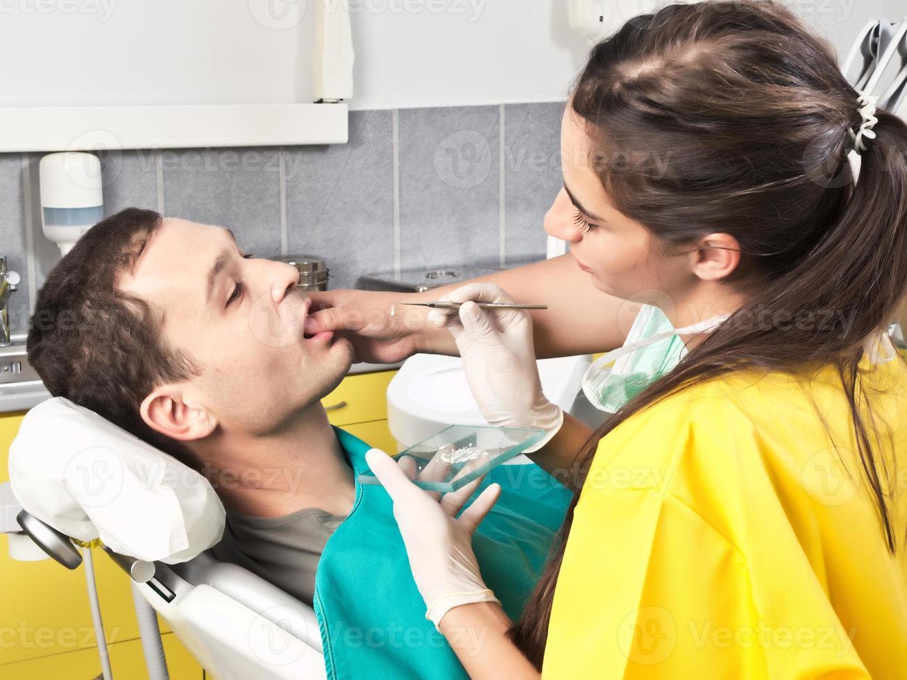 Zahnarzt überprüft die Zähne des Patienten foto