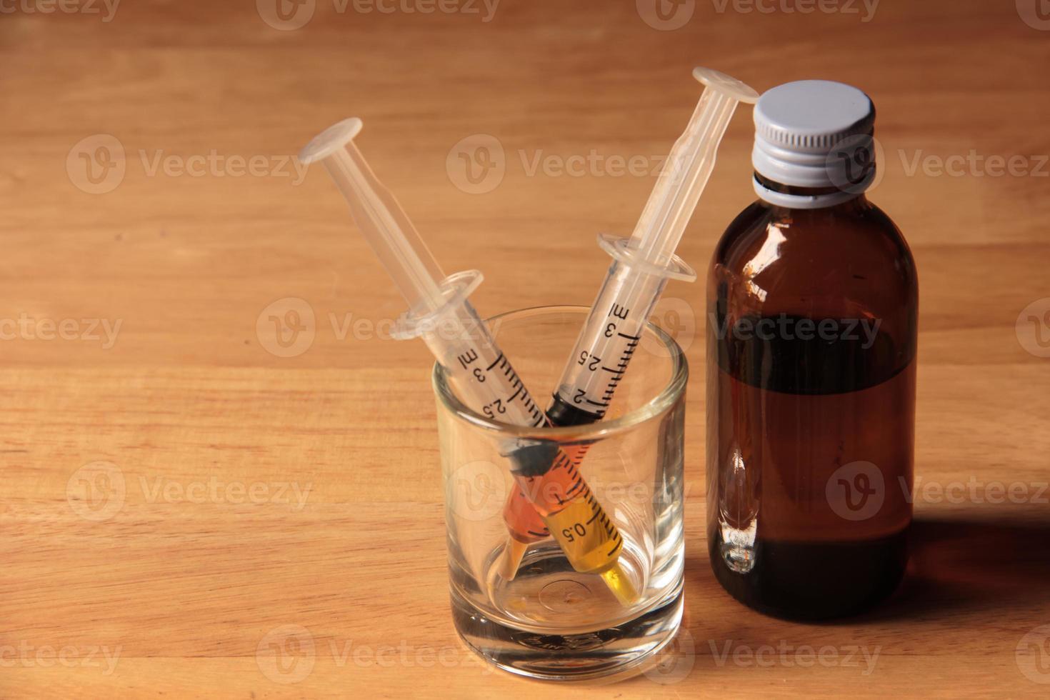 flüssiges Medikament und Spritze foto