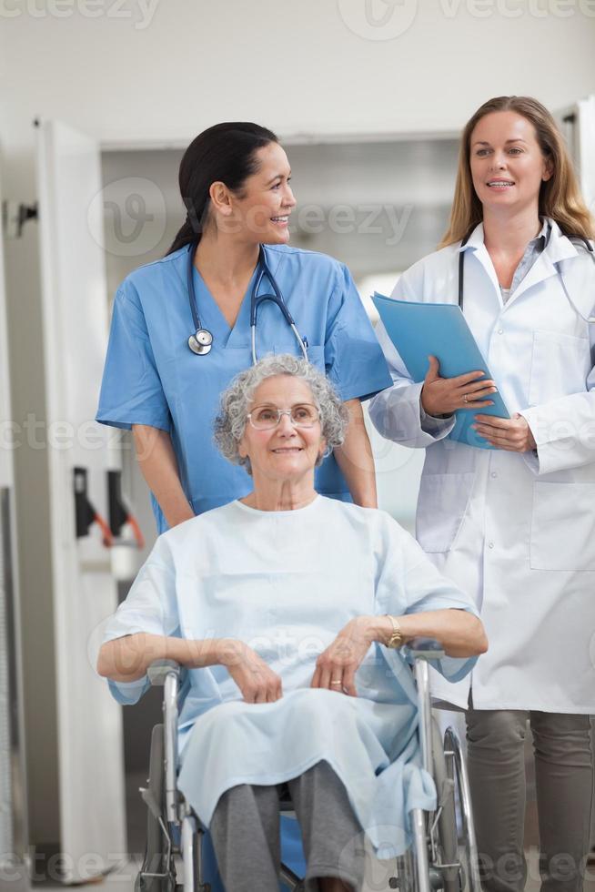 Krankenschwester rollt Patienten in einem Flur foto