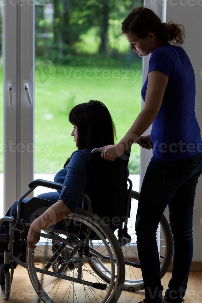 Pflegekraft, die Rollstuhl mit behinderter Frau schiebt foto