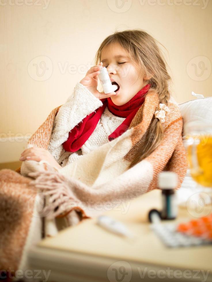 kleines Mädchen sitzt im Bett und benutzt Halsspray foto