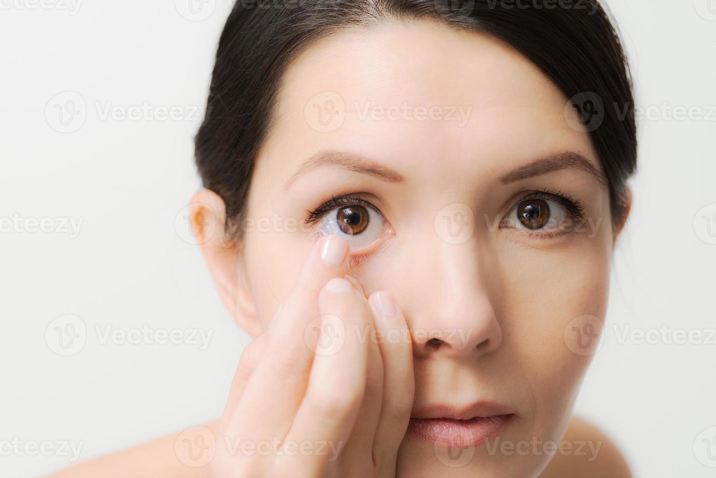 Frau im Begriff, eine Kontaktlinse in ihr Auge zu setzen foto
