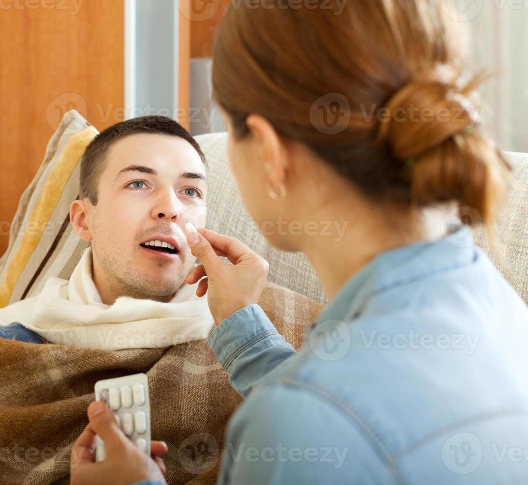 Frau gibt dem Ehemann Tabletten foto