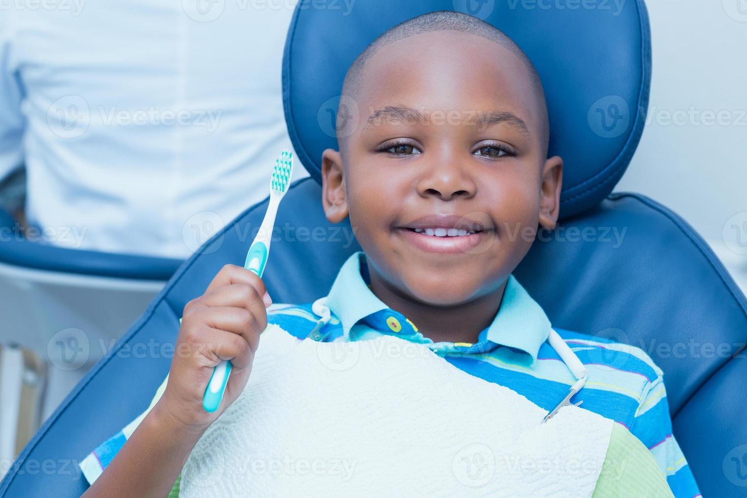 Junge, der Zahnbürste im Zahnarztstuhl hält foto