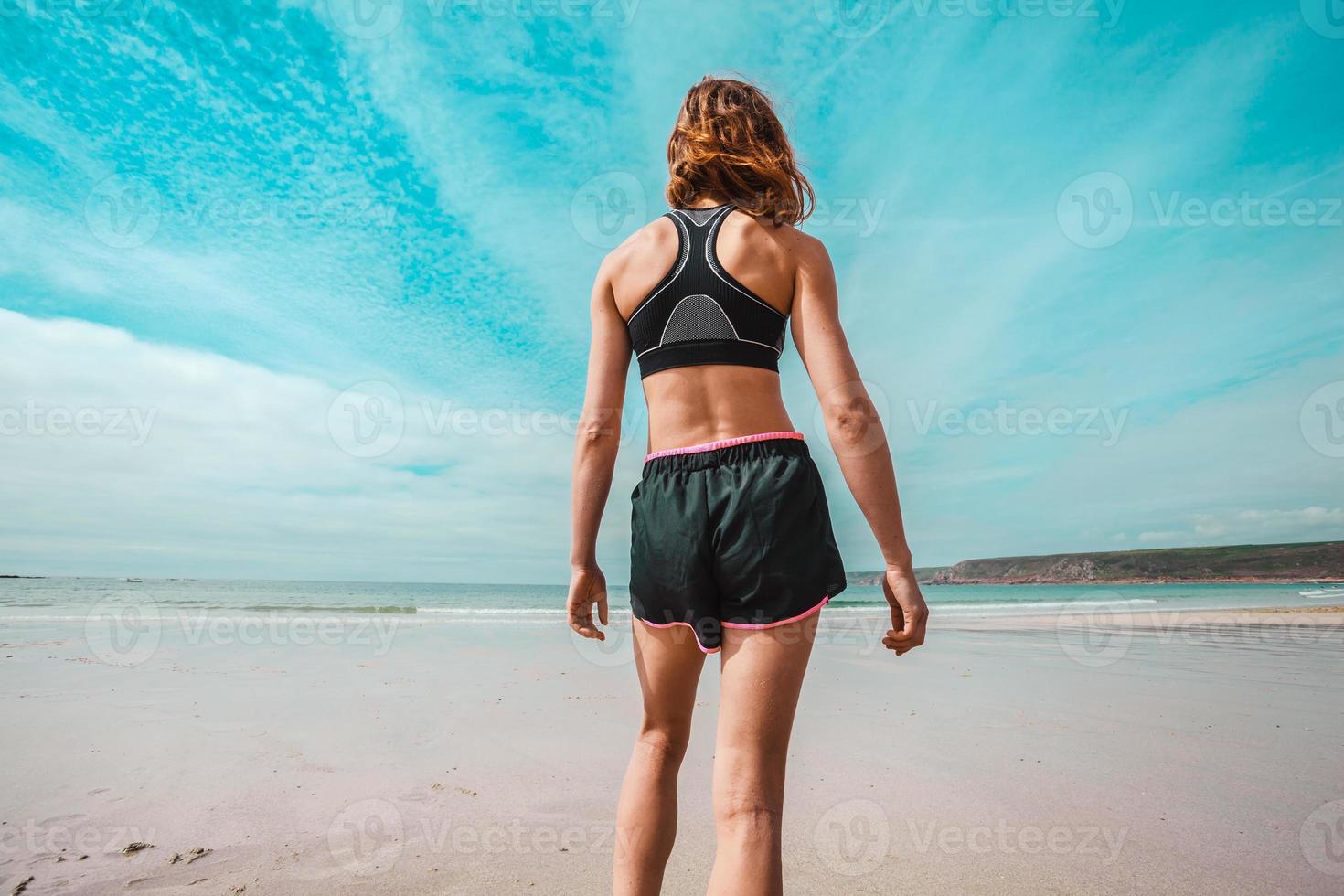 sportliche junge Frau, die am Strand steht foto