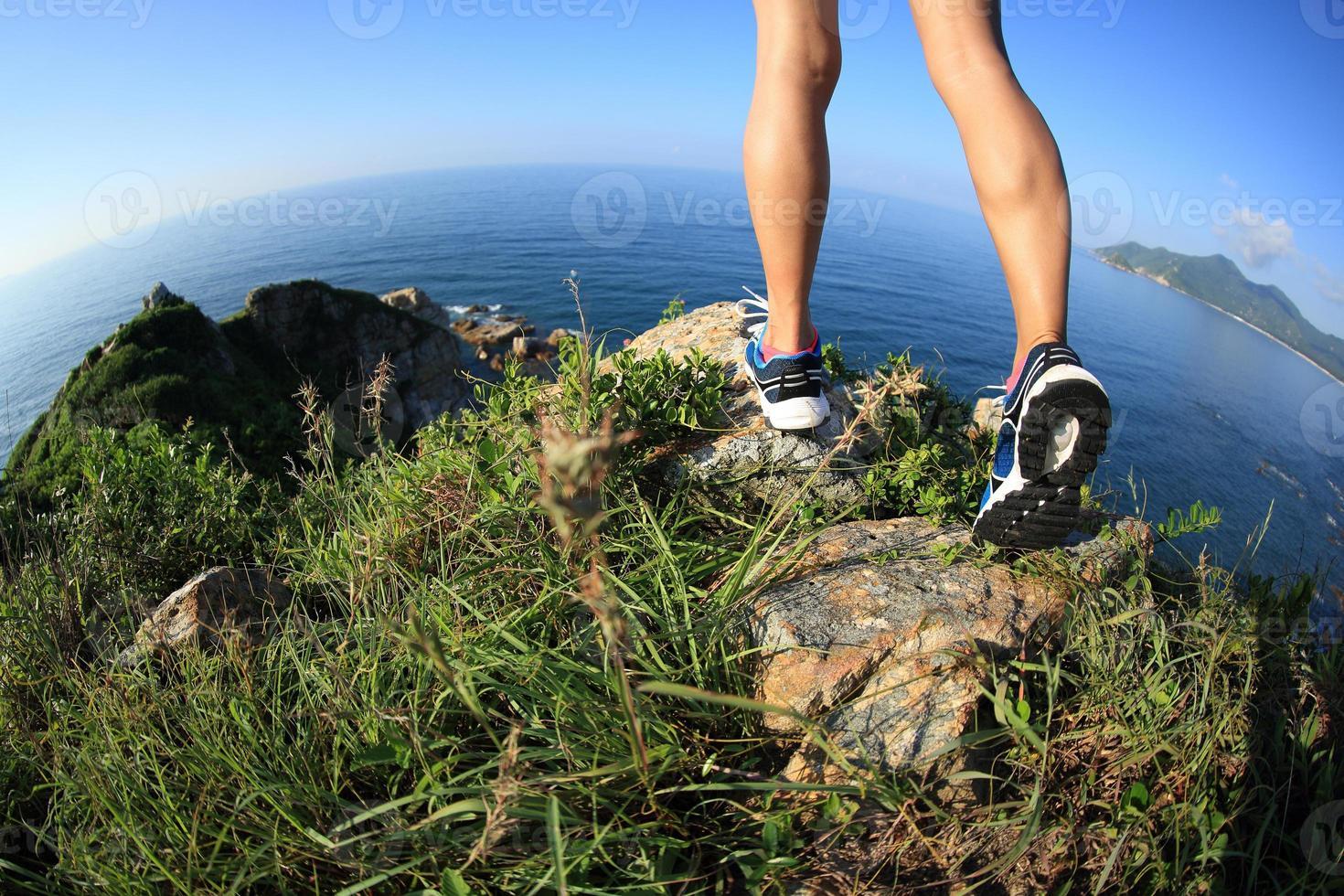 Frauenwandererbeine, die auf Berggipfel am Meer wandern foto