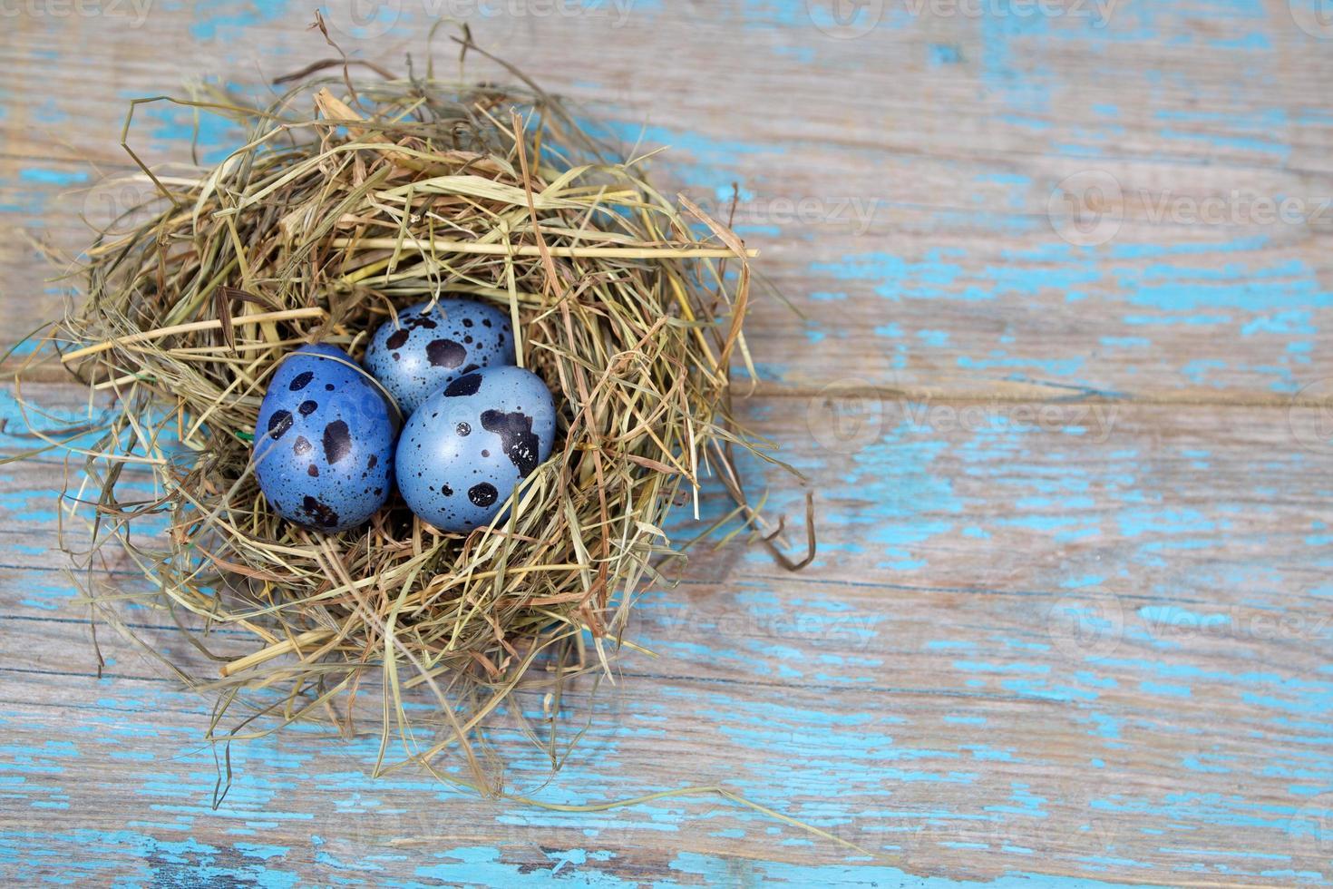 Osterdekorationen. Eier in Nestern auf hölzernem Hintergrund foto