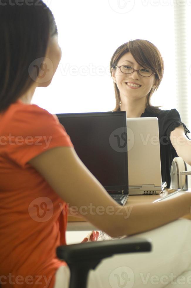 zwei junge japanische Frauen sprechen beim Betrachten des PCs foto