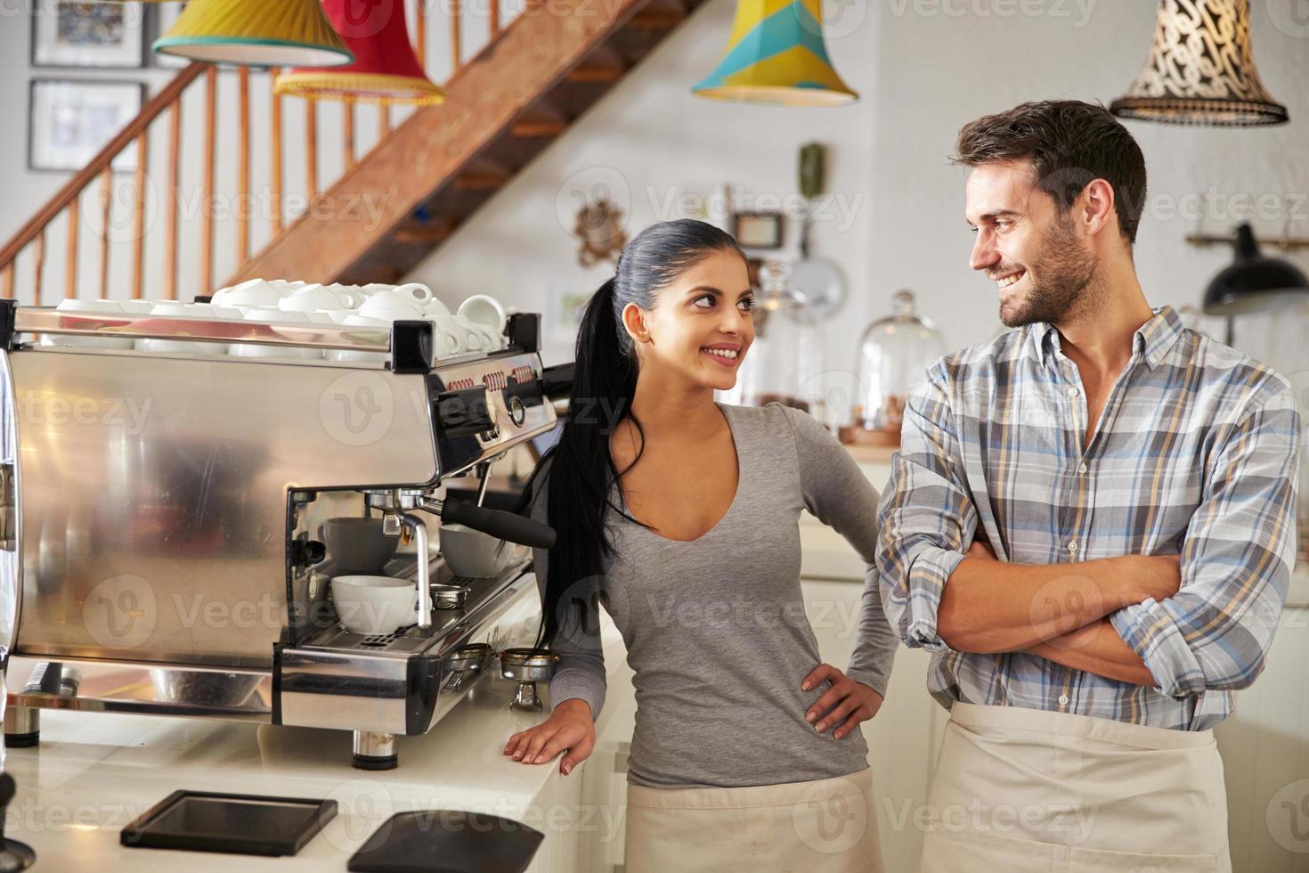 glückliche Caféarbeiter, die hinter der Theke stehen und lächeln foto