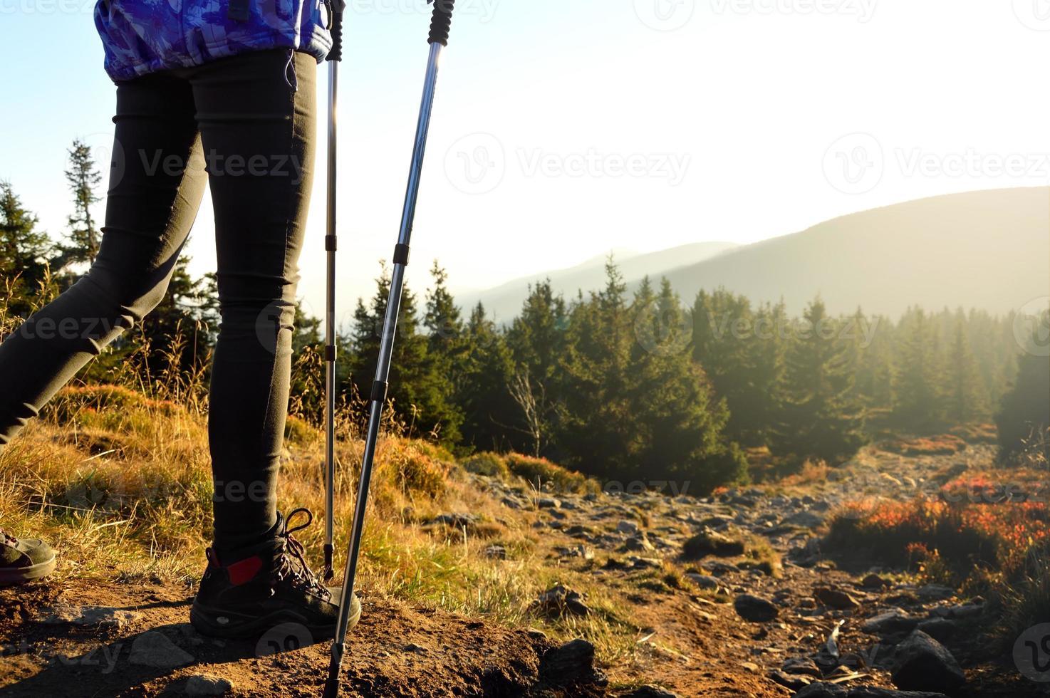 im Sonnenuntergang einen Bergpfad hinuntergehen. foto