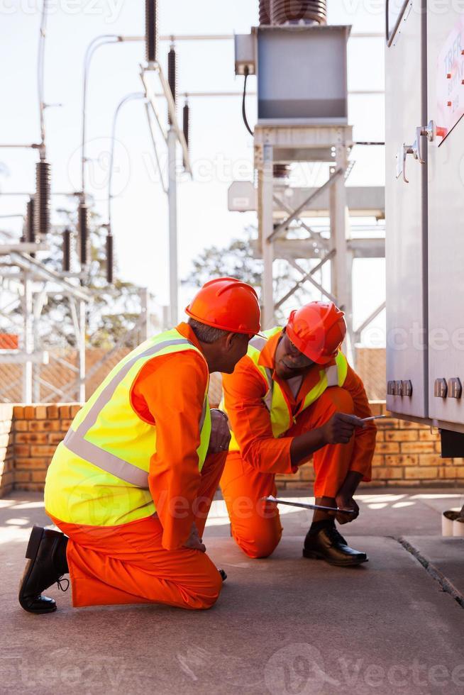 elektrische Mitarbeiter des Energieversorgungsunternehmens im Umspannwerk foto