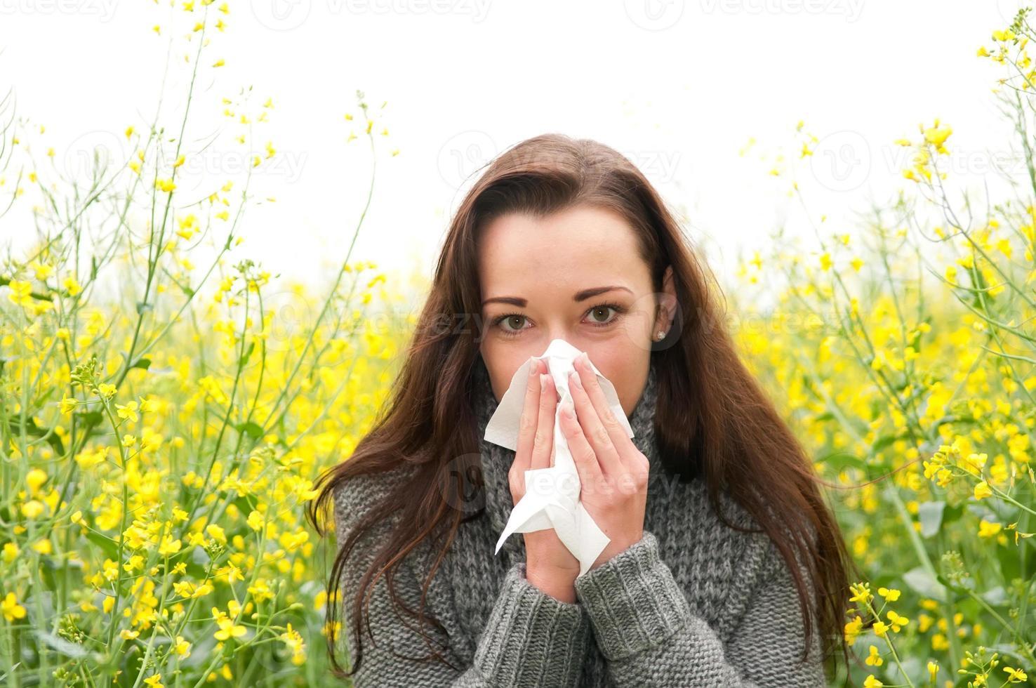 Frau, die Nase in einem Blumenfeld bläst foto