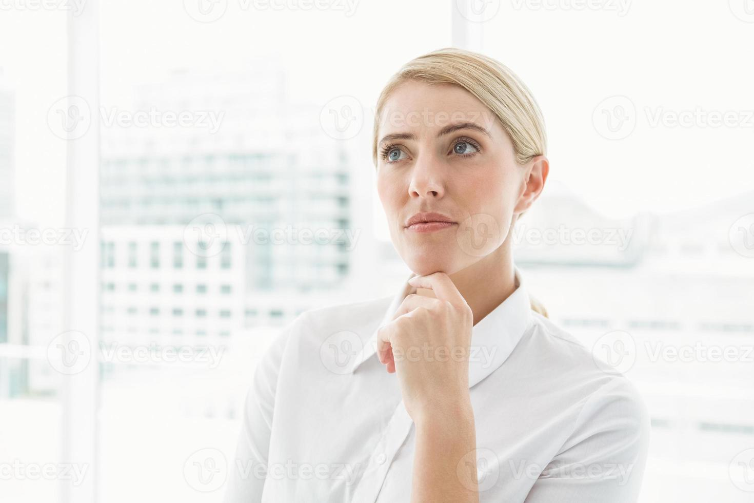 nachdenkliche Geschäftsfrau, die weg im Büro schaut foto