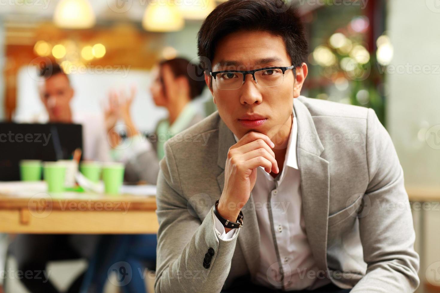 nachdenklicher asiatischer Mann, der im Büro sitzt foto