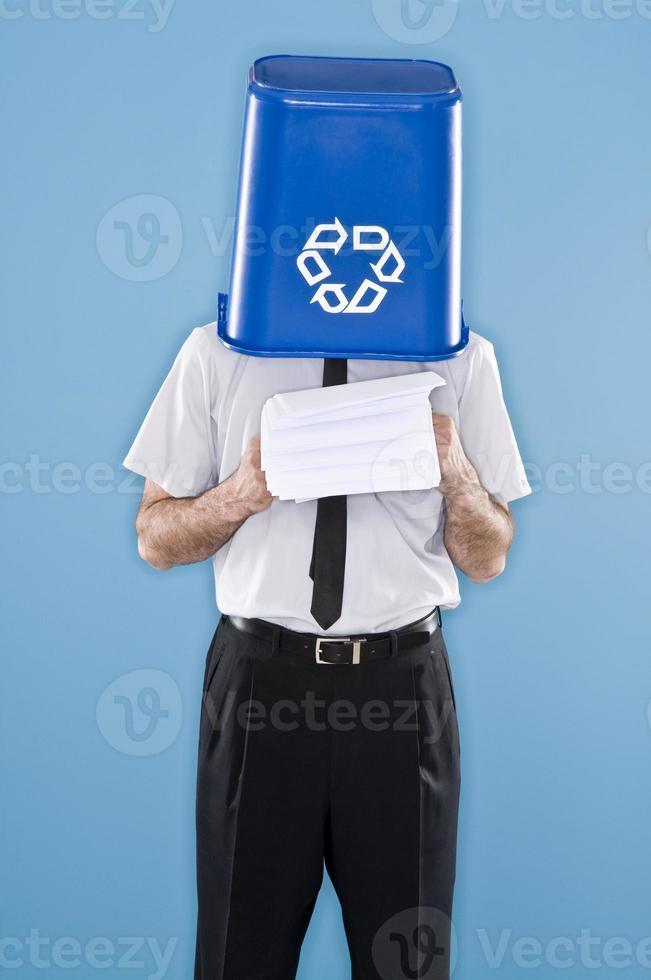Büroangestellter mit Kopf im Recyclingbehälter foto
