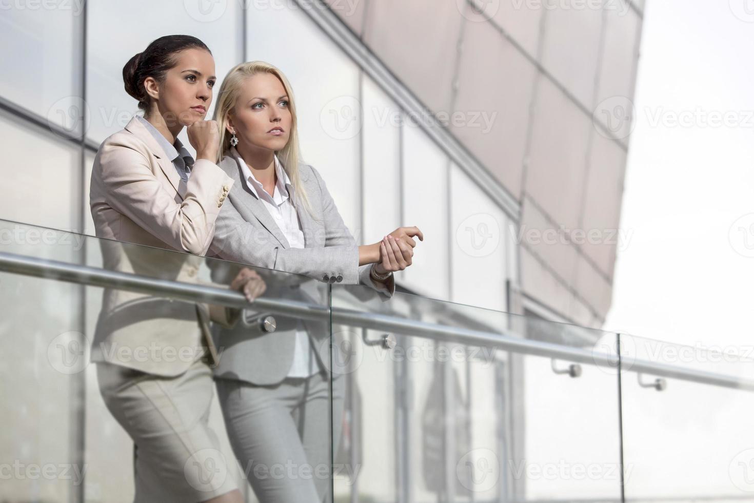 junge Geschäftsfrauen auf Bürogeländer schauen weg foto