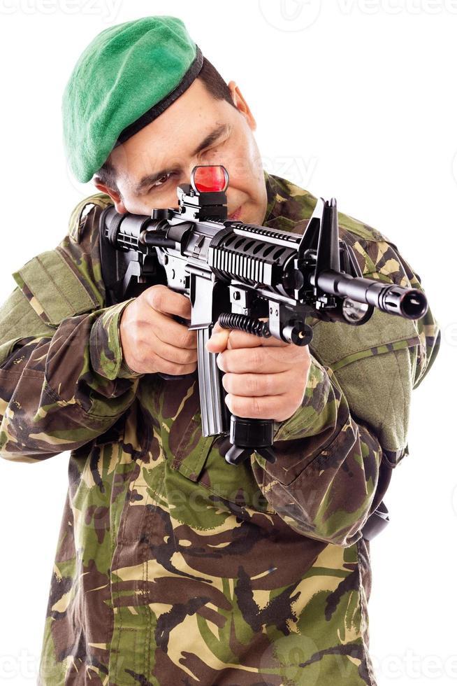 Porträt eines jungen Soldaten, der mit einer Waffe zielt foto