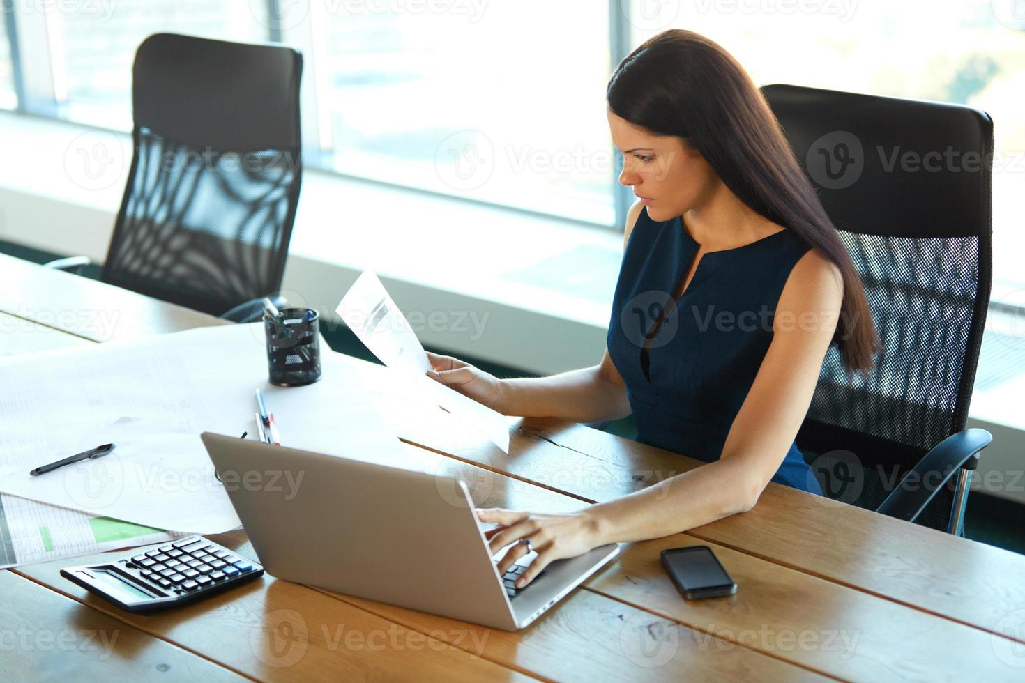 Porträt einer verwirrten Geschäftsfrau, die mit Papieren arbeitet foto