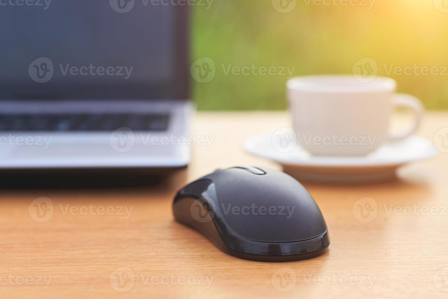 Nahaufnahme Maus mit Laptop und Kaffee auf dem Tisch foto