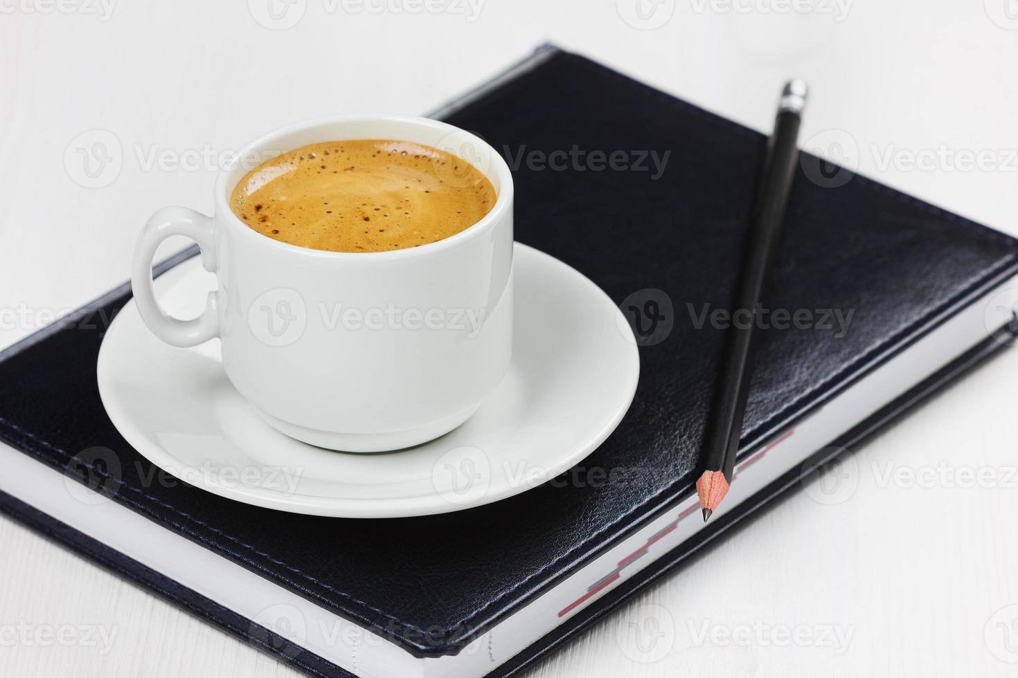 Arbeitsplatz mit Geschäftstagebuch, Bleistift und Tasse Kaffeepause foto