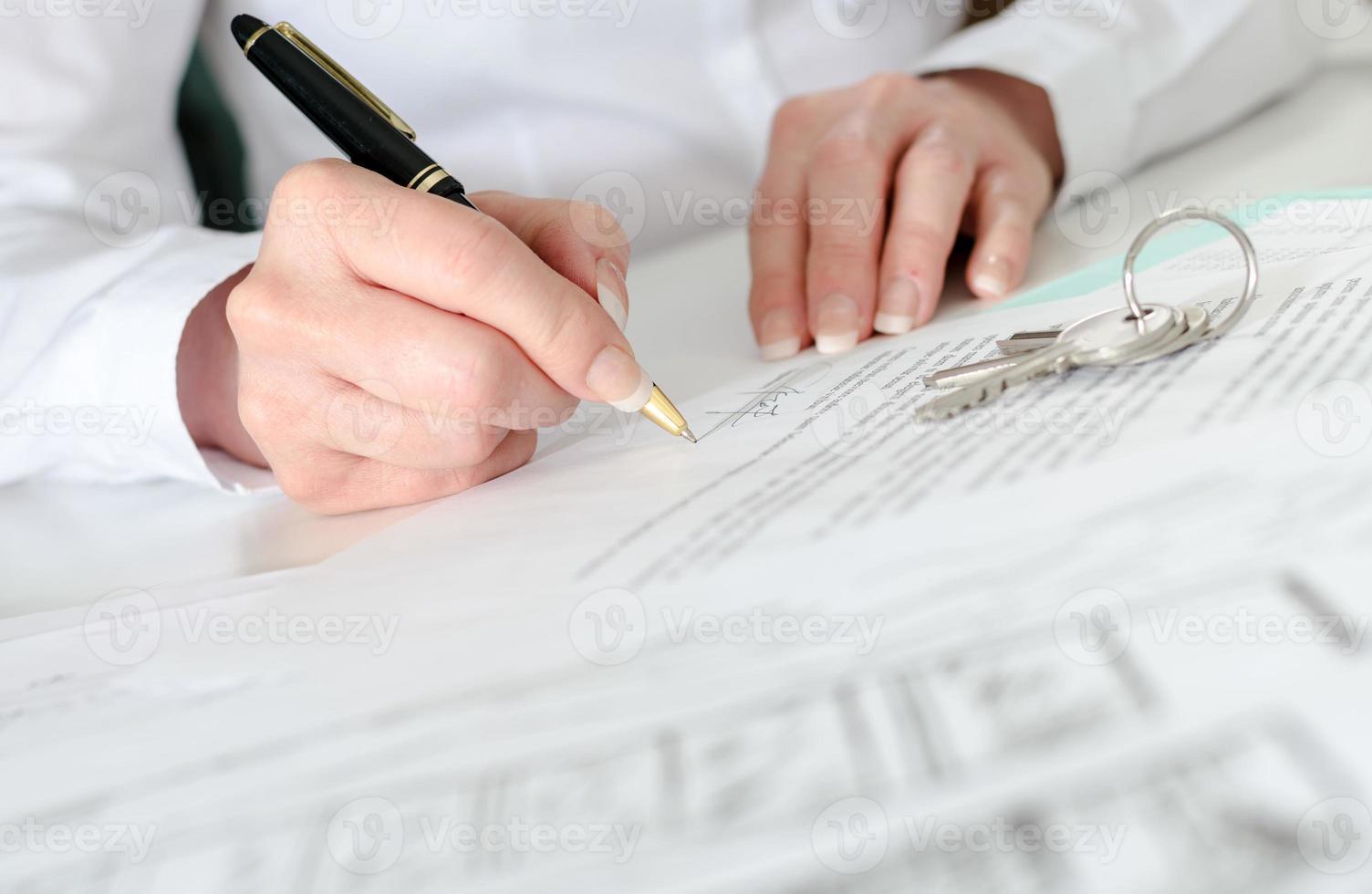 Kunde unterzeichnet einen Immobilienvertrag foto
